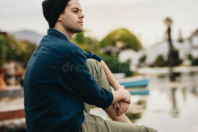 Side view of a man sitting near a lake looking away. Man relaxing on a holiday enjoying the scenic beauty of the lake stock photos