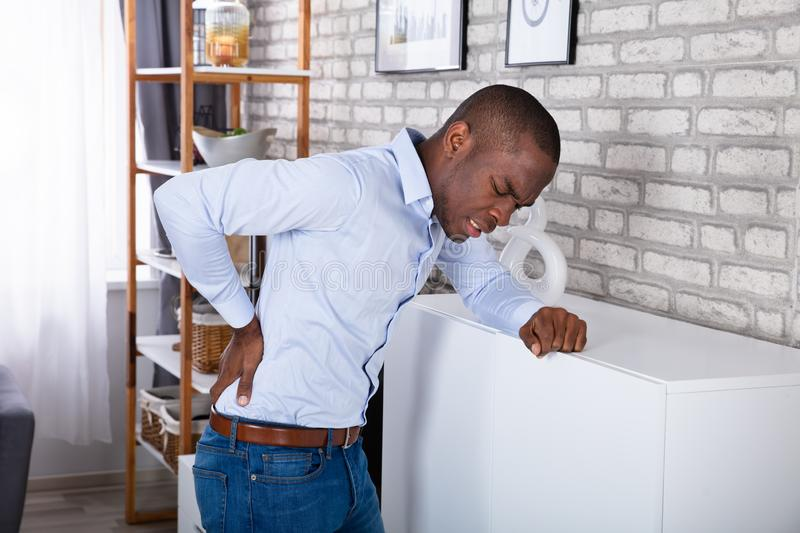 Side View Of A Man Suffering From Back Pain stock image