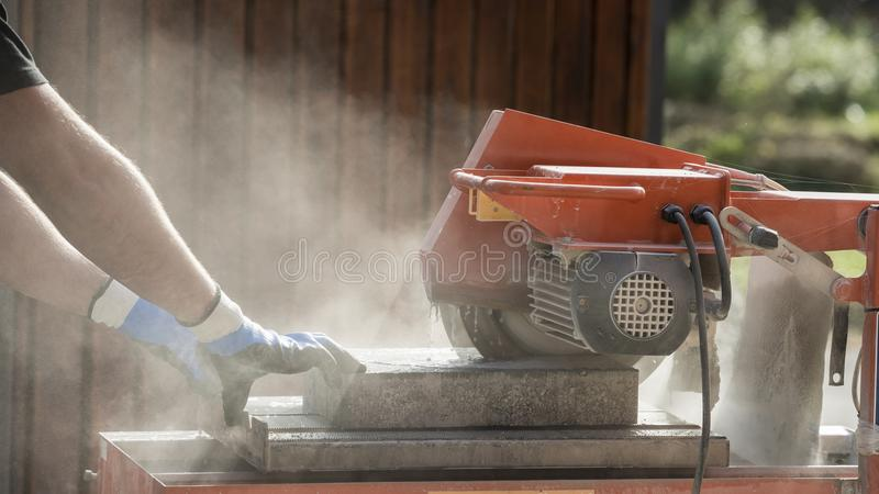 Side view of a man using an angle grinder stock images