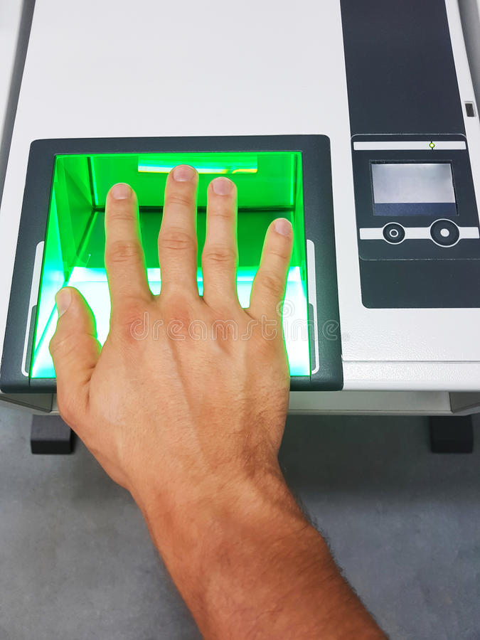Side view from a man using a fingerprint scanner for identification. Biometrics or cybersecurity concepts. Man uses a high-tech device for identification stock image