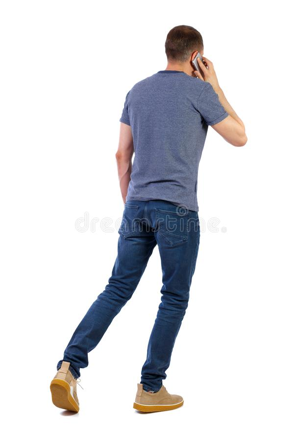 A side view of man walking with a mobile phone royalty free stock photo