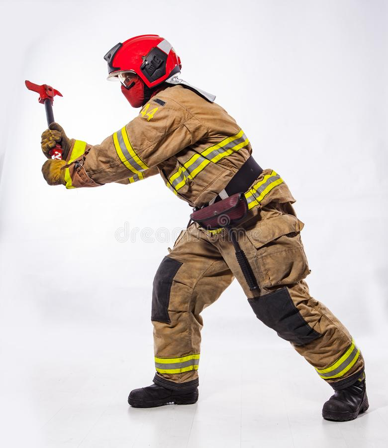 Fire fighter with ax on white. Side view of man wearing uniform and helmet of fire fighter and holding special ax standing on white background royalty free stock images