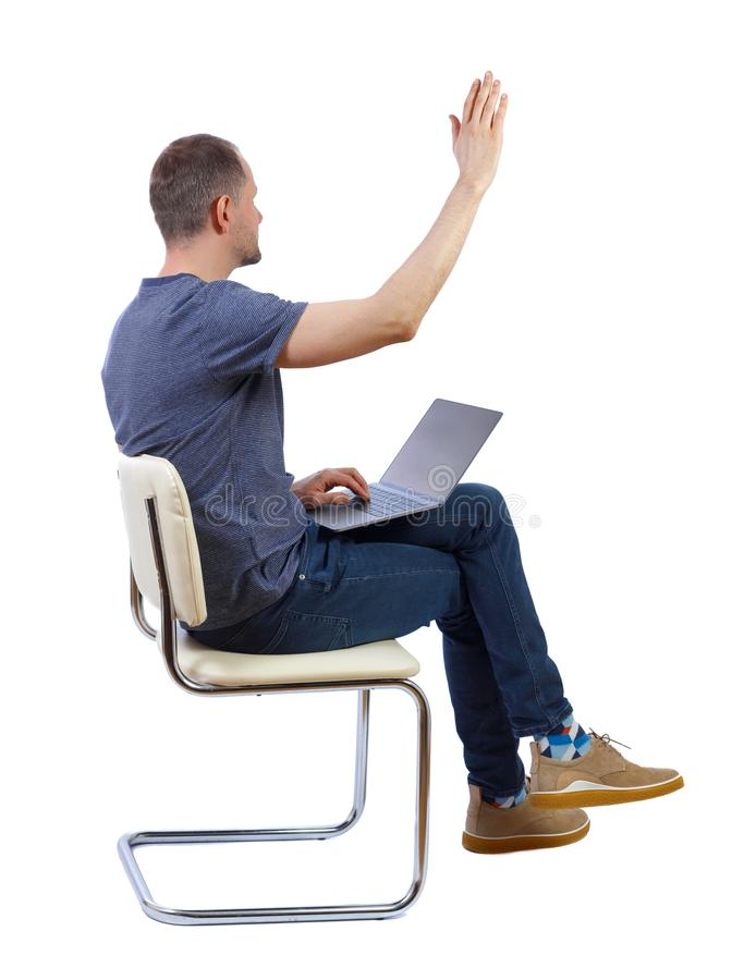 Side view of a man who sits on a chair with a laptop and points with his hand forward royalty free stock image