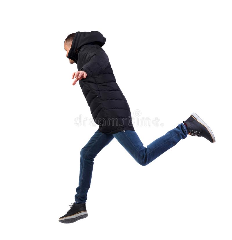 Side view of a man in a winter jacket who jumps stock image