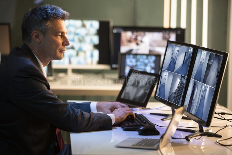 Businessman Looking At CCTV Camera Footage. Side View Of A Mature Businessman Looking At CCTV Camera Footage On Multiple Computer Screen stock images