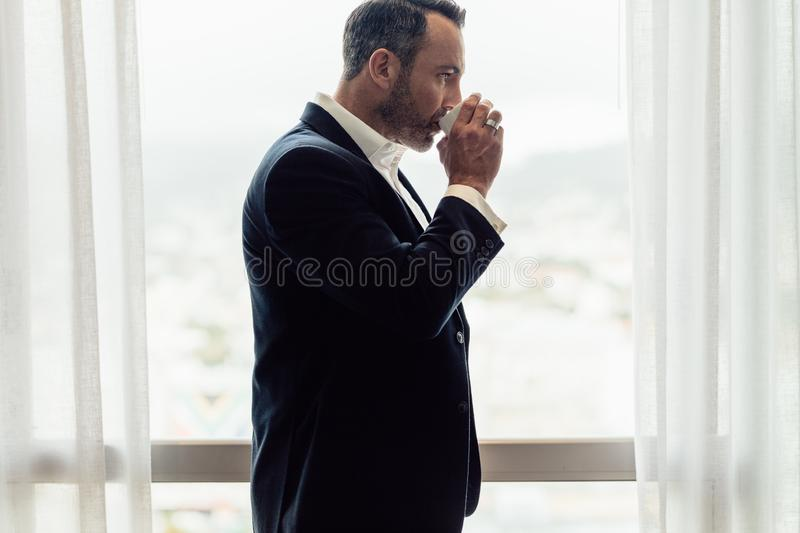 Side view of mature businessman in suit drinking coffee in hotel room. Business traveler in hotel room having coffee.  stock photos