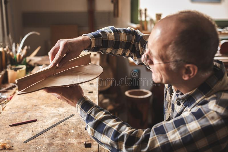 Instrument maker checking his workpiece with a wooden template. Side view of a mature instrument maker that is working at a rustic workbench inside a traditional royalty free stock photography