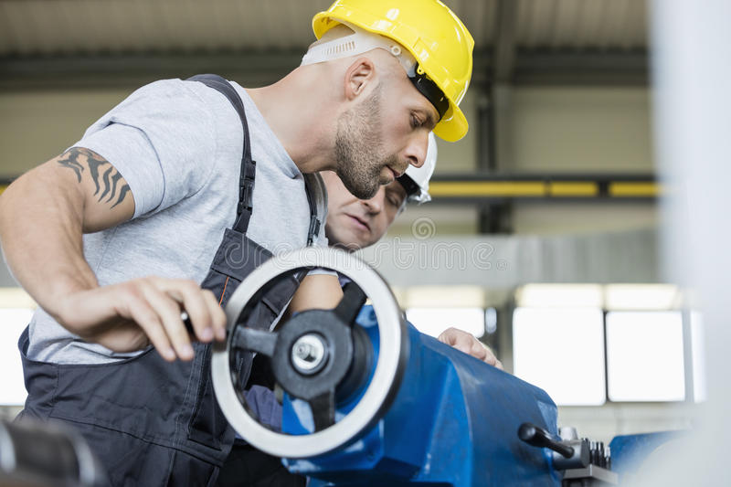 Side view of mid adult worker with colleague operating machinery in industry royalty free stock images