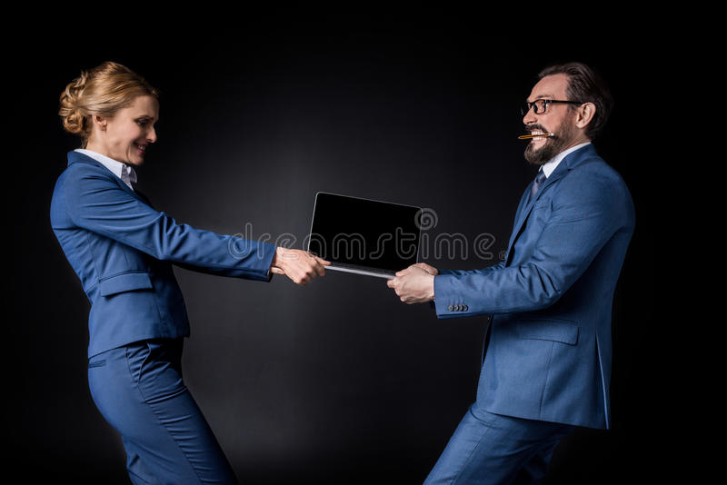 Side view of middle aged business colleagues fighting for laptop stock photography