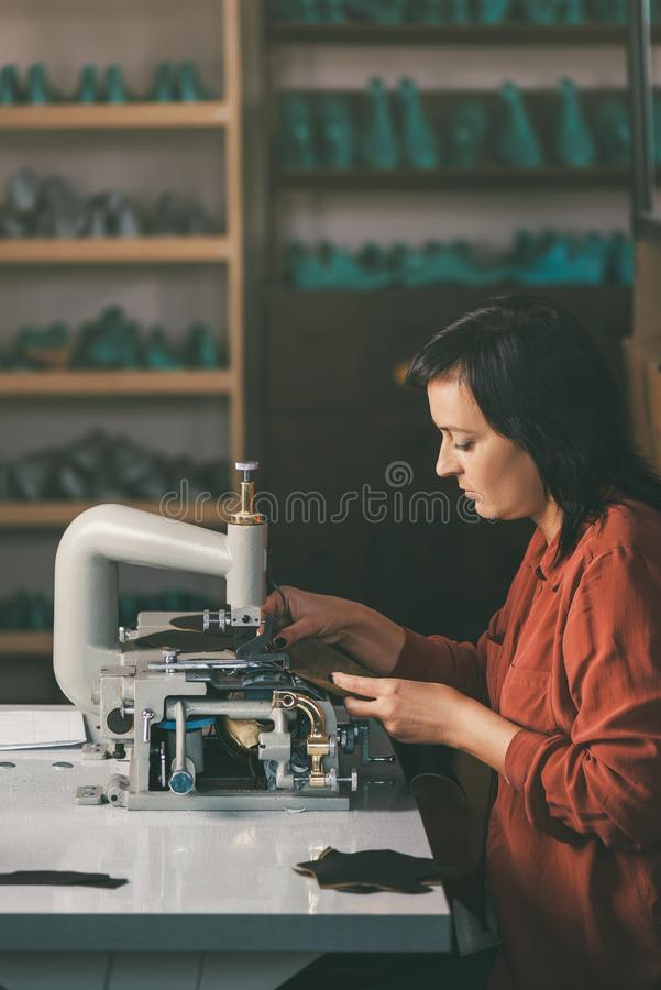 Side view of middle aged seamstress working with sewing machine and leather at shoemaker. Workshop royalty free stock photo