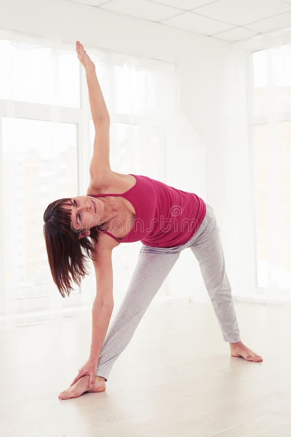 Side view of middle-aged woman doing stretching exercises in the stock images