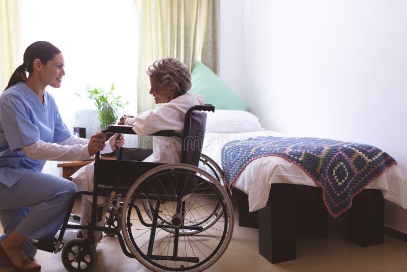 Nurse talking with senior female patient at nursing home stock image