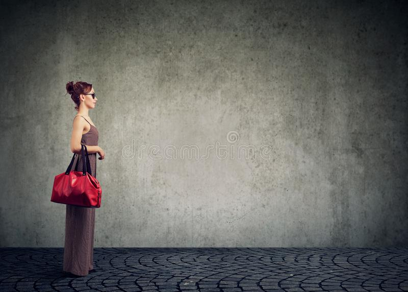 Modern trendy woman in sunglasses and dress standing with bag on gray background stock images