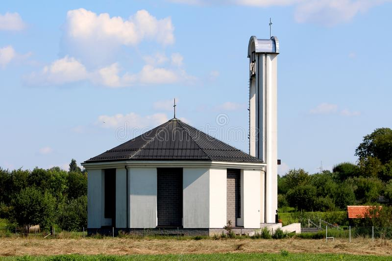 Side view of modern unusually built white and grey catholic church with tall bell tower with iron cross on top. And large ringing bell mechanism in middle royalty free stock image