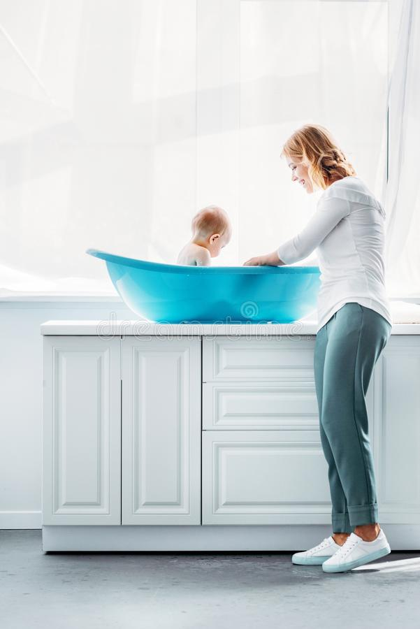 Side view of mother bathing child. In plastic bathtub at home stock images