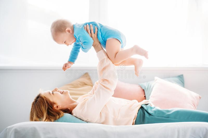 Side view of mother raising laughing little child. While lying on bed at home royalty free stock image