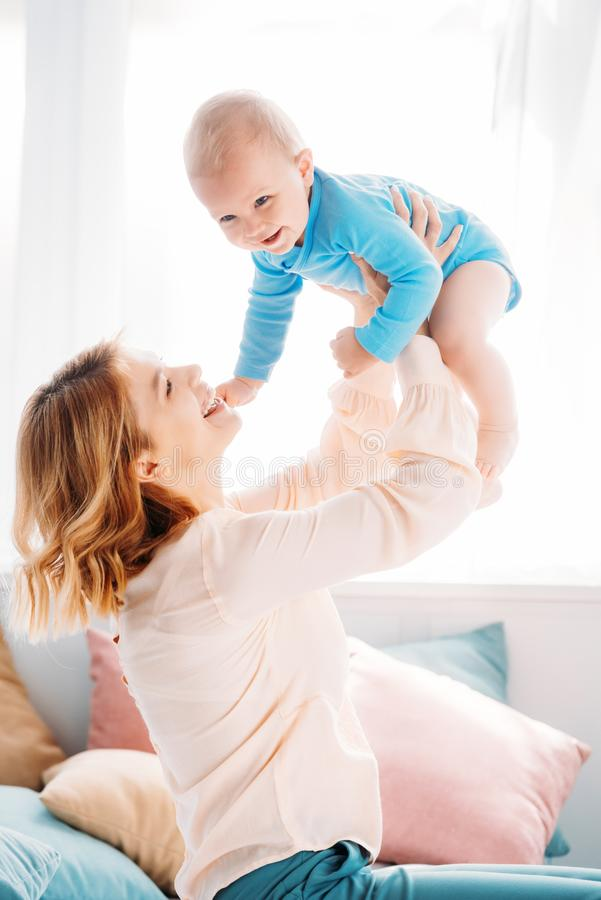 Side view of mother raising laughing little child. While sitting on bed at home stock images