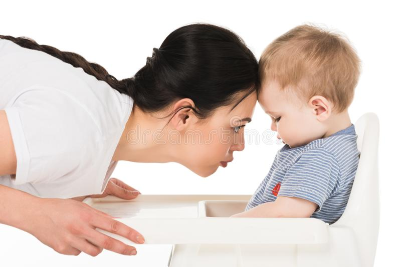 side view of mother touching forehead of little son sitting in highchair stock image