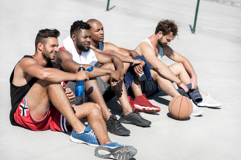 side view of multicultural basketball team resting after game royalty free stock images