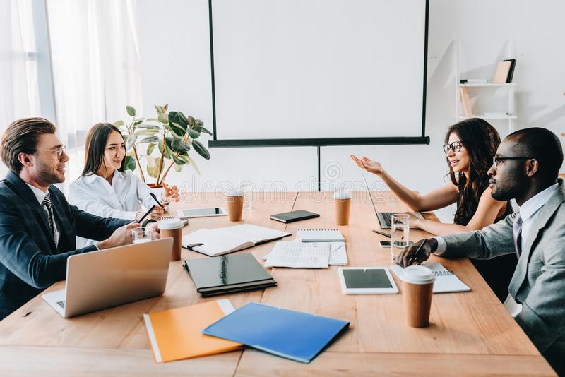 side view of multicultural business people having business meeting stock photography