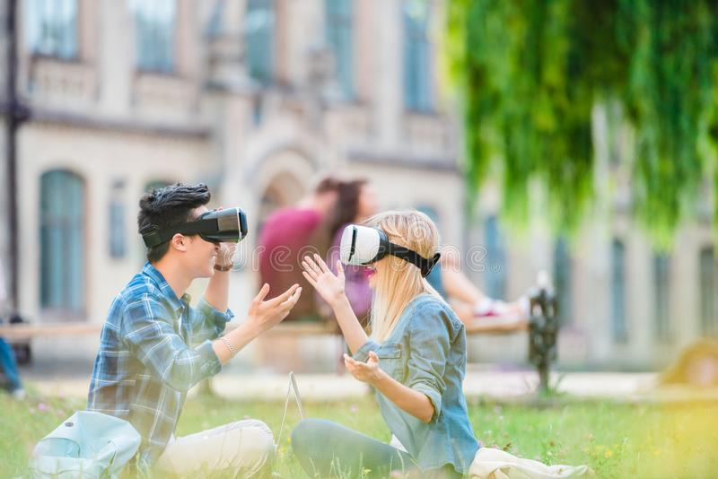 Side view of multicultural students in virtual reality headsets with laptops sitting on green grass. In park stock photos
