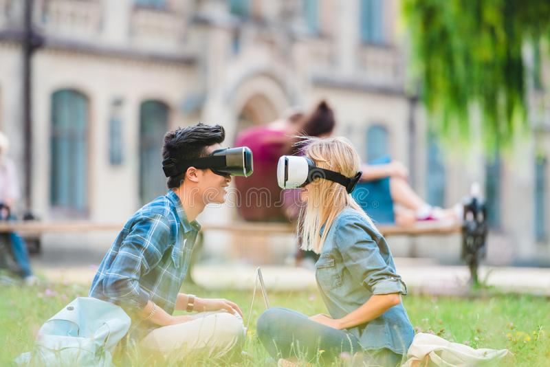 Side view of multicultural students in virtual reality headsets with laptops sitting on green grass. In park royalty free stock photos