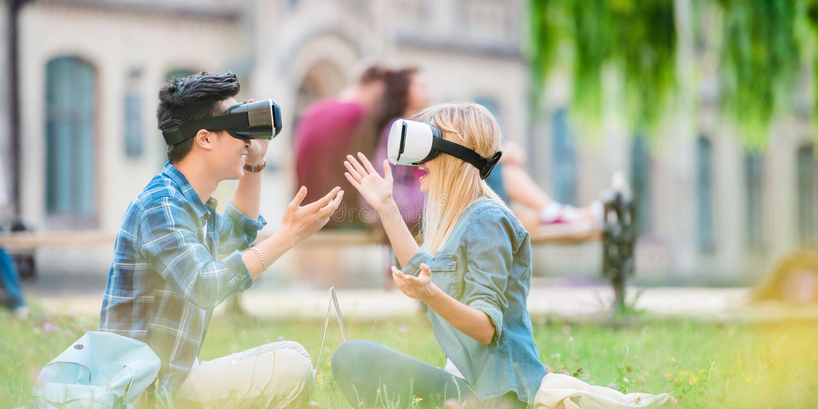 Side view of multicultural students in virtual reality headsets with laptops sitting on green grass. In park stock images