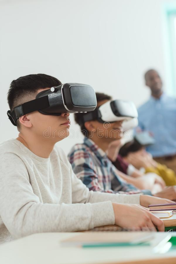 Side view of multiethnic high school pupils using virtual reality headsets and teacher. Standing behind stock photo
