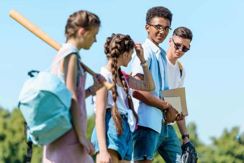 side view of multiethnic teenage students with books backpacks and sport equipment walking together stock photos