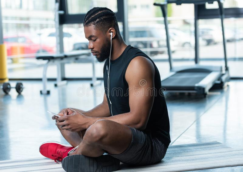 Side view of muscular african american man. In earphones using smartphone while sitting on yoga mat in gym stock photo