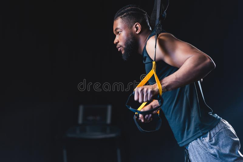 Side view of muscular african american man. Exercising with resistance bands and looking away stock image