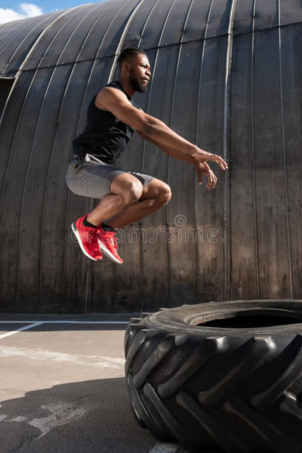 Side view of muscular african american man. Jumping while training with tyre on street stock photo