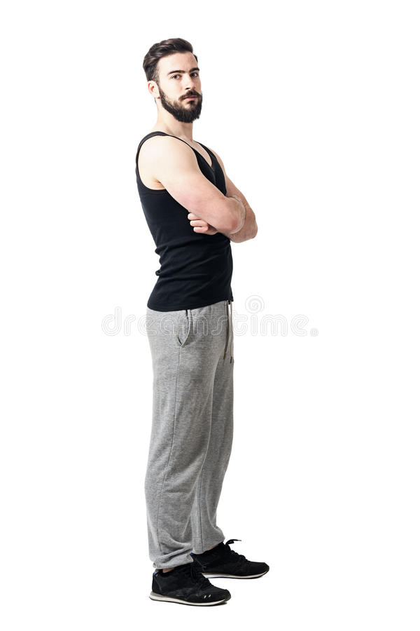 Side view of muscular athlete in tank top with crossed arms looking at camera. Toned desaturated full body length portrait isolated on white studio background royalty free stock photography