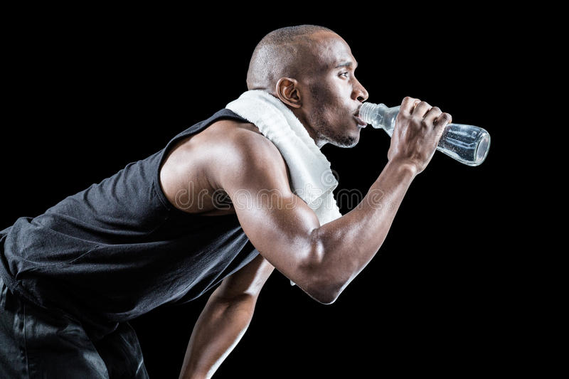 Side view of muscular man drinking water while bending stock photos
