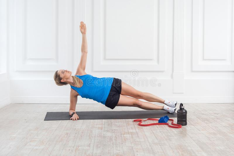 Side view of muscular sporty beautiful blonde young athletic caucasian woman in black shorts and blue top standing on perfect side. Elbow plank position. Indoor stock images