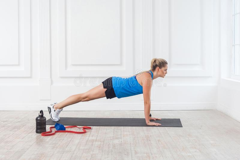 Side view of muscular sporty strong young athletic beautiful caucasian woman in black shorts and blue top standing on perfect. Plank position. Indoor, studio stock photos