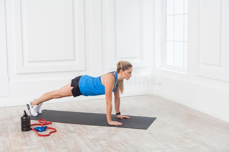 Side view of muscular sporty strong young beautiful athletic caucasian woman in black shorts and blue top standing on perfect. Plank position. Indoor, studio royalty free stock photography
