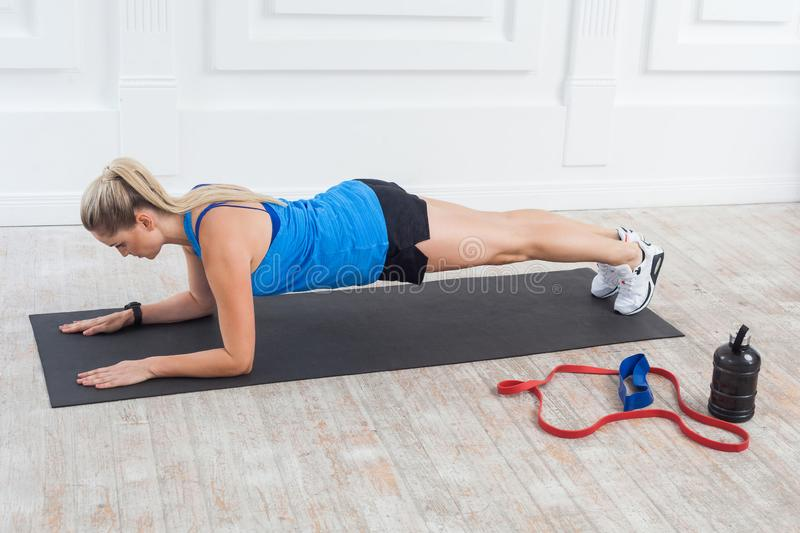 Side view of muscular sporty strong young beautiful athletic caucasian woman in black shorts and blue top standing on perfect. Elbow plank position. Indoor stock photo