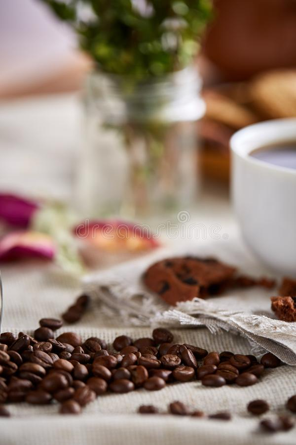 Roasted coffee beans get out of overturned glass jar on homespun tablecloth, selective focus, side view royalty free stock image
