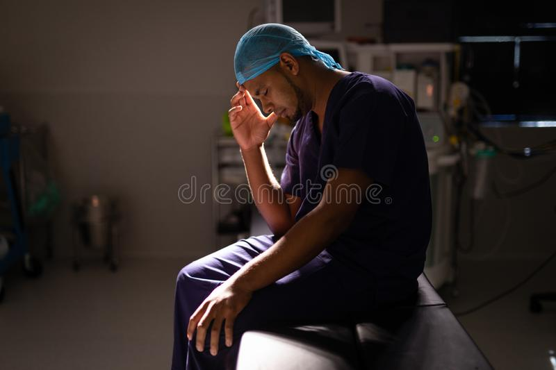 Nervous male surgeon sitting in operation room at hospital royalty free stock photo