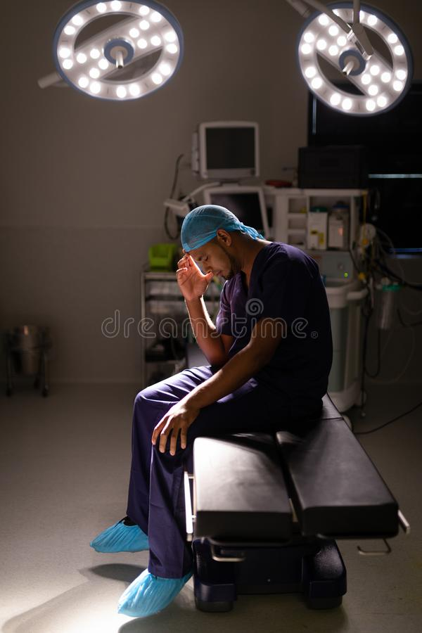 Nervous male surgeon sitting in operation room at hospital stock photos