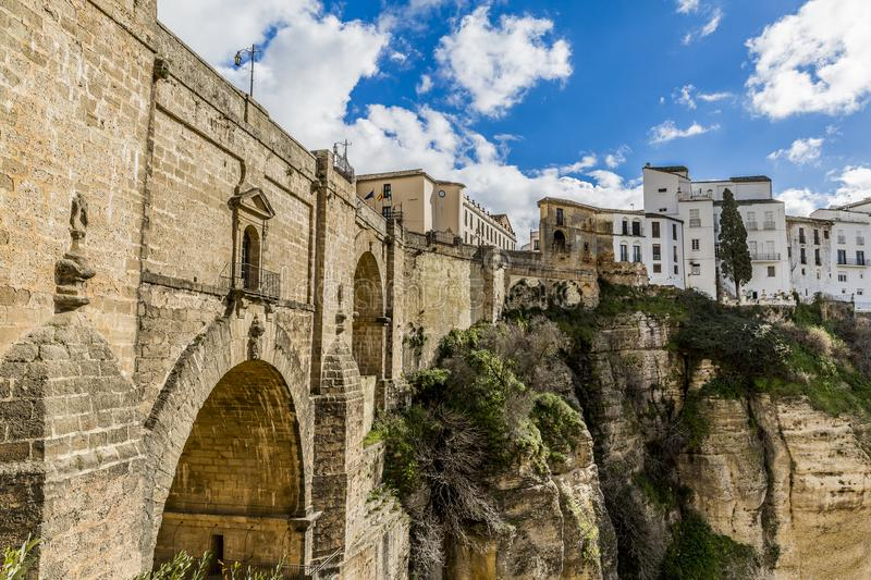 Side view of the New Bridge, Puente Nuevo and a small part of the city of Ronda over a mountainous area. Wonderful and sunny day with abundant white clouds in royalty free stock photography