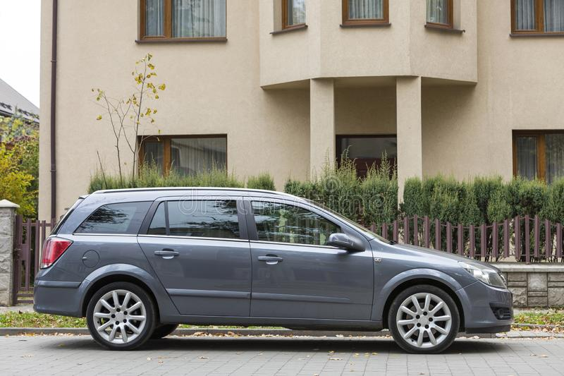 Side view of new family gray car parked in paved parking lot in front of big cottage. Luxury and prosperity concept stock photo