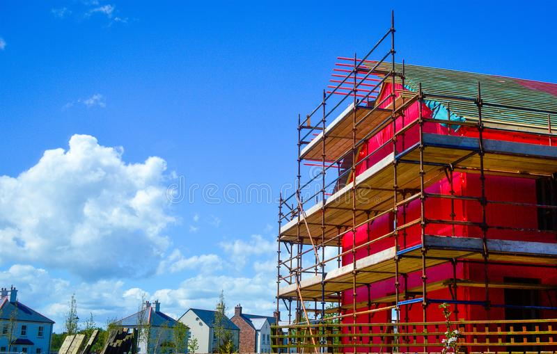 Side view of a new two-storey house under construction with red protective layer, scaffolding and wooden boards. stock image