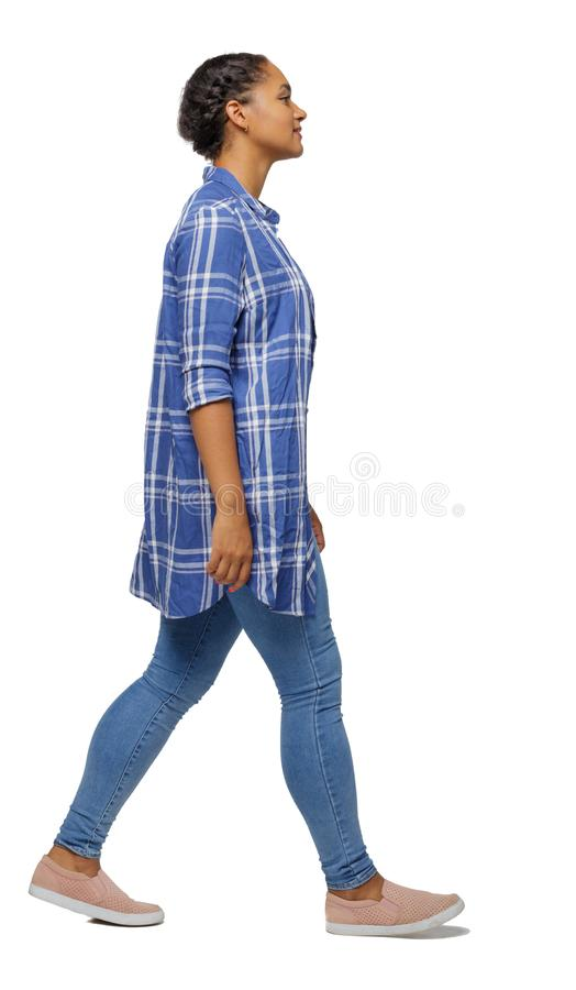 Free Side View Of A Young Black Girl Walking In Jeans And A Checkered Shirt Stock Photography - 141052172