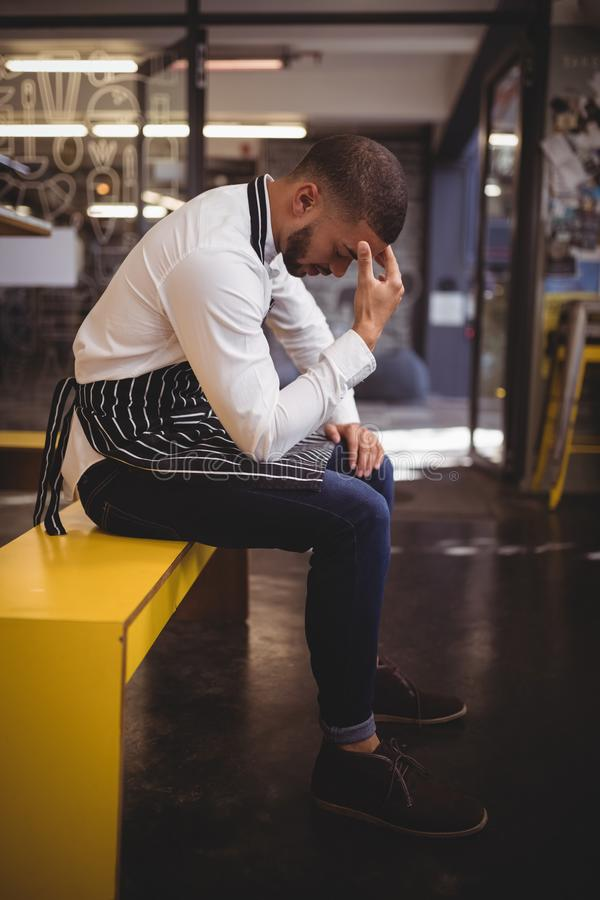 Free Side View Of Upset Young Waiter Sitting On Yellow Bench With Headache Stock Images - 99469164