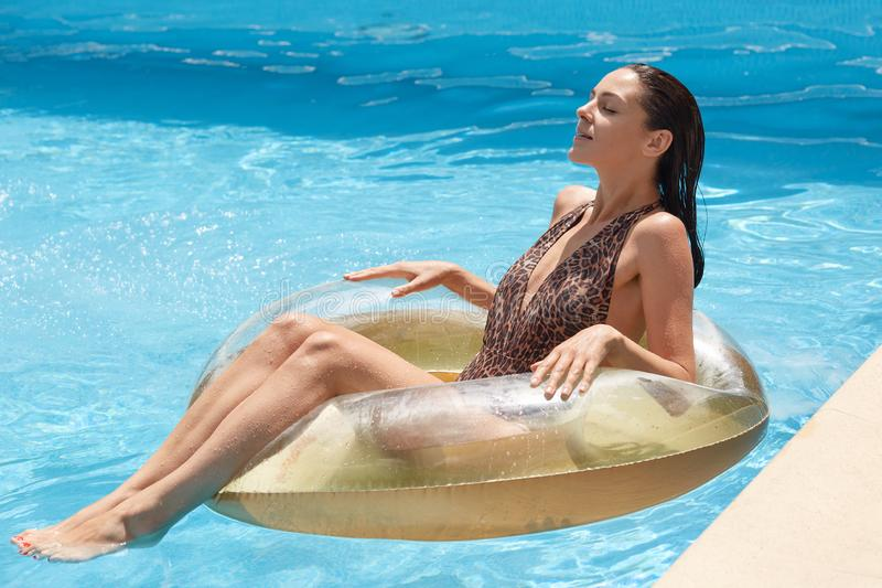Side view og slim tanned woman in swimming suit with leopard print, looks while lyingon inflatable ring in swimming pool, spending stock photo