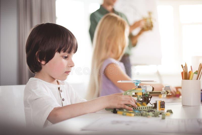 Serene child creating robot at desk stock photo
