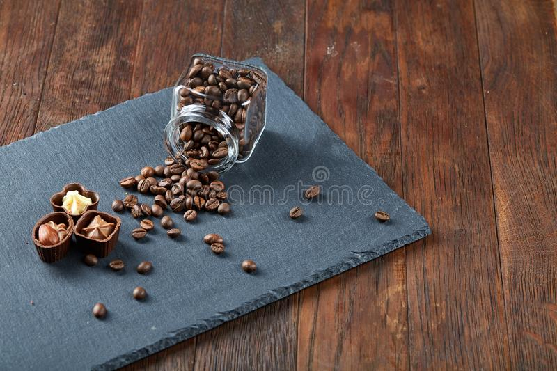 Side view of overturned glass jar with coffee beans and chocolate candies on wooden background, selective focus stock photo