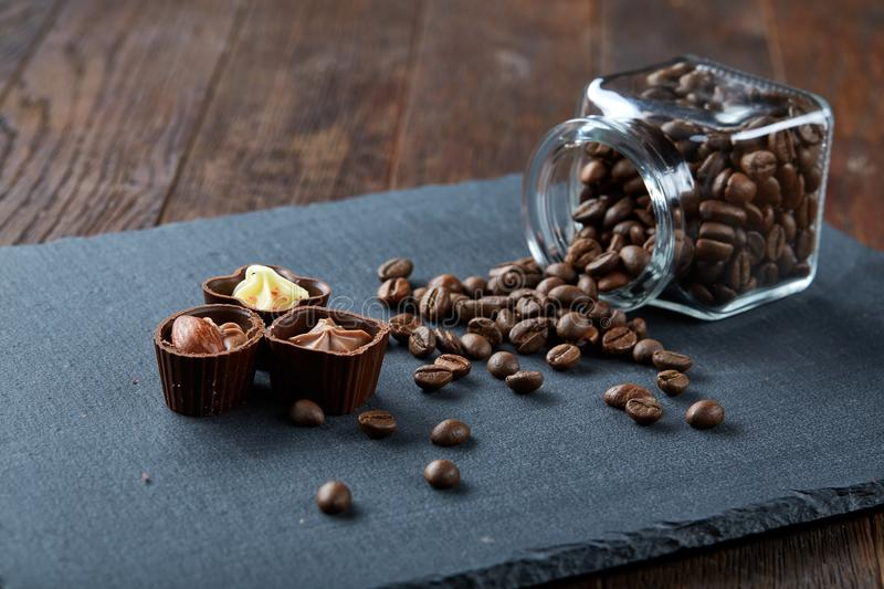 Side view of overturned glass jar with coffee beans and chocolate candies on wooden background, selective focus royalty free stock photos